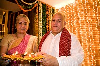 Old couple holding a tray of diyas