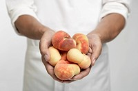 Chef holding peaches (mid section)