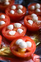 Group of tomatoes and mozzarella cheese on aluminum foil.