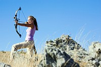 Young woman arrow shooting in field