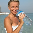 Woman drinking from water bottle on beach, close_up