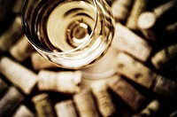 High angle view of a wine glass surrounded by corks
