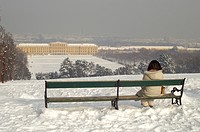 Female tourist sits on a bench looks to palace Schönbrunn in winter Vienna Austria