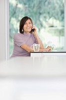 Woman having tea and talking on cell phone