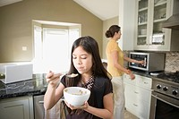 Girl eating bowl of cereal in kitchen