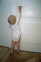 Little one year old child tries to open a door