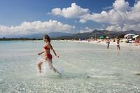 Woman running in water at Cala Brandinchi Beach eastcoast Sardinia Italy