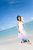 Portrait of a young woman walking on beach, smiling, Saipan, USA