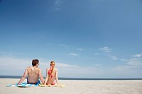 Young couple sitting at beach and looking at view rear view, Spring Lake, New Jersey, USA
