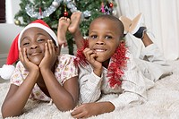 Girl wearing a Christmas hat lying on the floor next to her brother.