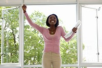 Businesswoman standing at open windows celebrating, Cape Town, Western Cape Province, South Africa