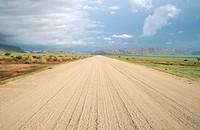 View of dirt road leading through semi arid area. Naukluft Mountains, Namibia.