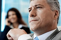 Businessman Thinking, Woman on Phone in Background