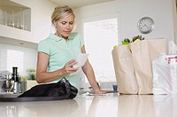 Mature woman checking receipts in kitchen low angle view
