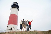 Five people jumping by lighthouse low angle view
