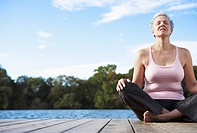 Mature woman sitting crossed legged by lake, eyes closed