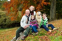 Portrait of grandparents, grandkids, and dog sitting on tree stump