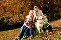 Family and dog sitting on tree stump in woods
