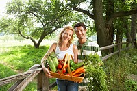 Husband and wife with fresh vegetable basket portrait