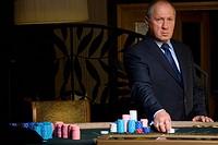 Mature man gambling, hand on chips, portrait