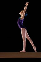 Young female gymnast 9_11 performing on balance beam, side view