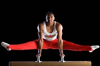 Male gymnast performing on pommel horse, portrait, low angle view
