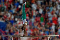 Male gymnast performing handstand on parallel bars, side view