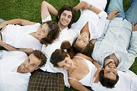 Six young people lying on grass portrait, directly above