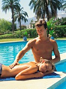 Man massaging woman near swimming pool