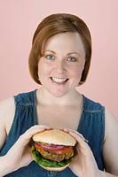 Mid_adult woman holding hamburger