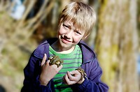 Common European toad ( Bufo bufo ) lying on the hand of a nine-year-old child