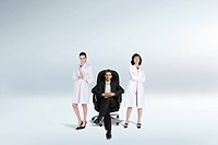 business man sitting on chair beside stand_up woman doctor