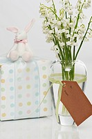 Flowers in vase with wrapped gift