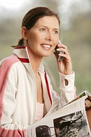Woman, about 45 years old, with mobile-phone and magazine
