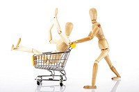 Jointed wooden mannequin pushing a shopping cart