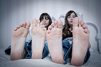 Close_up of preteen twin sisters feet as they sit on a bed in their bedroom.