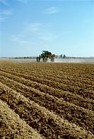 Agriculture _ A John Deere sprayer applies liquid fertilizer to a freshly bedded cotton field / AR.