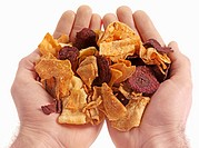 Hands holding assorted dried vegetable crisps