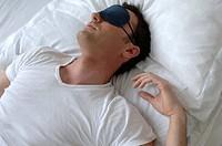Man sleeping in bed, wearing a sleep mask