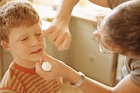 Father putting ointment on boy´s face