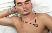Young man lying on back, hand behind head resting
