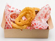 Deep_fried onion rings with ketchup in a cardboard box