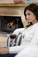 Woman, living room, couch, sitting, wine glass, chimney fires,