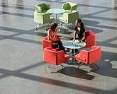 Two business colleagues having a meeting over a hot drink in an office building