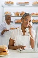 African woman using telephone in bakery