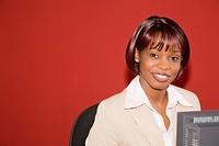 portrait of black businesswoman sitting behind computer