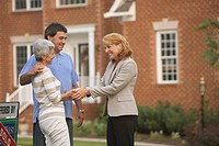 Hispanic couple shaking hands with real estate agent