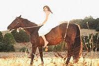 Hispanic woman riding bareback in sunlight