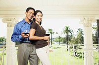 Couple leaning on balcony railing at resort