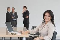Portrait of Hispanic businesswoman next to laptop